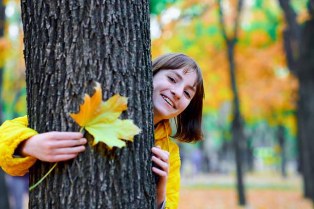 adolescente chica posando con hojas de otoño en el parque de la ciudad, retrato al aire libre - foto de stock