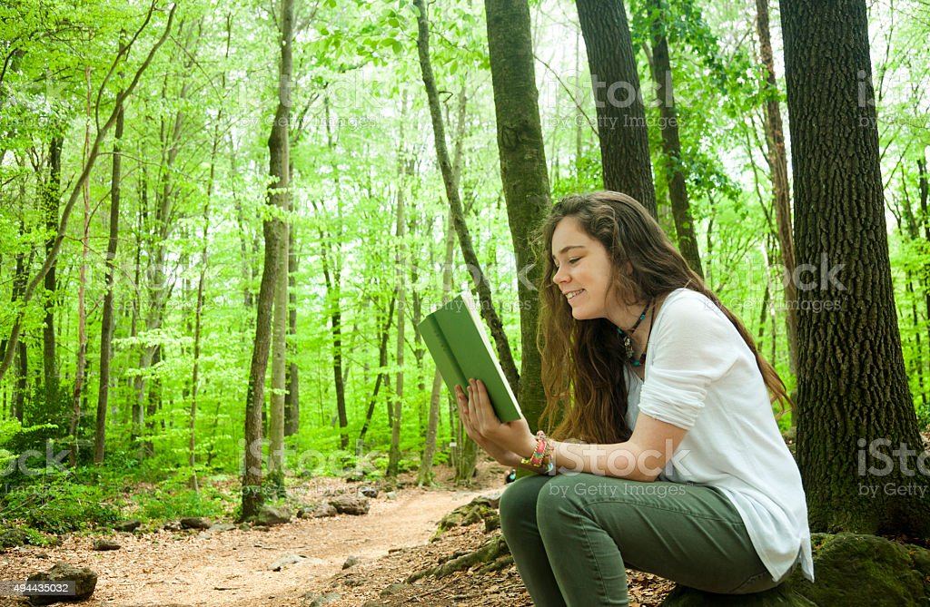 Teen girl reading alone in a forest stock photo