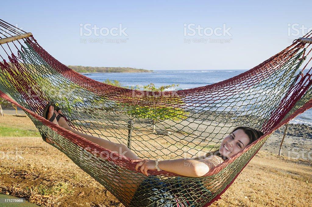 Teen girl relaxing in hammock stock photo
