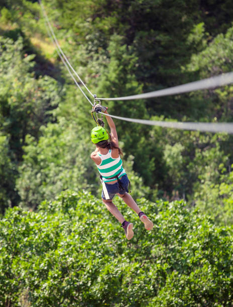 Teen girl riding a zipline through the forest. View from behind Diverse Teen girl riding a zip line in a lush mountain forest while on vacation. View from behind. Lots of copyspace zip line stock pictures, royalty-free photos & images