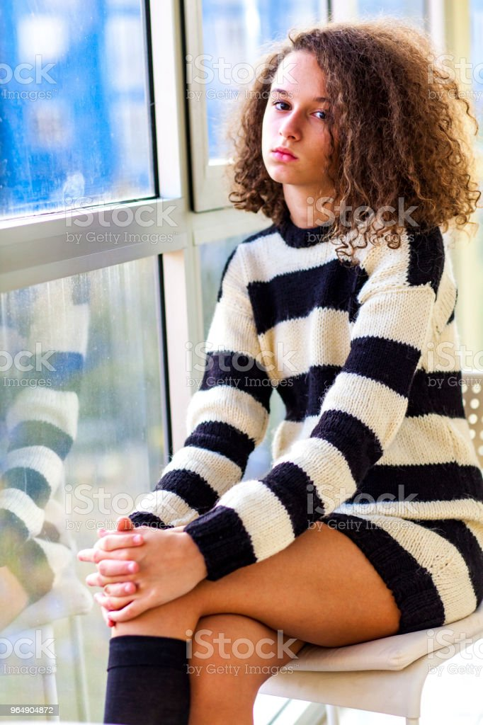 Teen girl sitting by window royalty-free stock photo