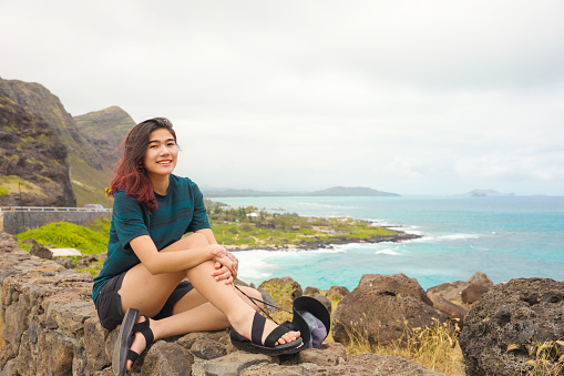 Biracial Asian Caucasian teen girl sitting on top of rock stone wall at Makapu'u Lookout looking out over blue Pacific ocean on Oahu island with mountains and ocean horizon in background on cloudy overcast day