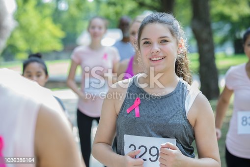 Teenage or preteen Caucasian girl smiles while running in breast cancer awareness charity race. Young runner is wearing a pink ribbon on her athletic clothing.