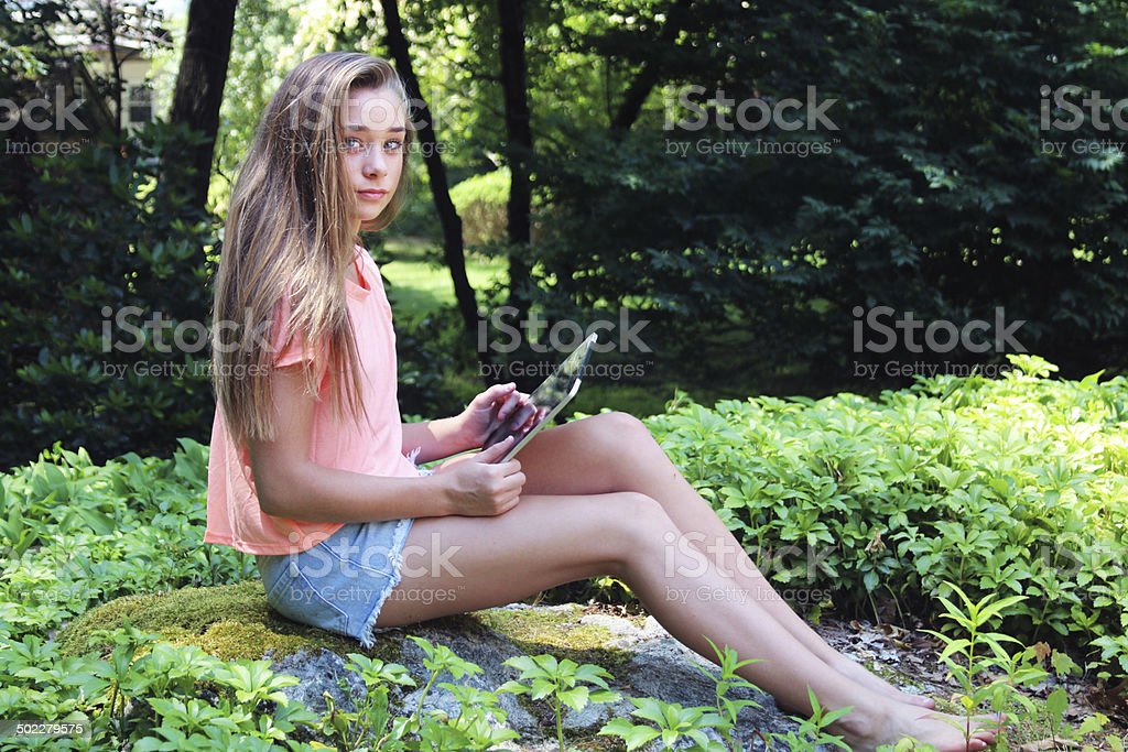Teen girl smiles with touch pad outdoors royalty-free stock photo