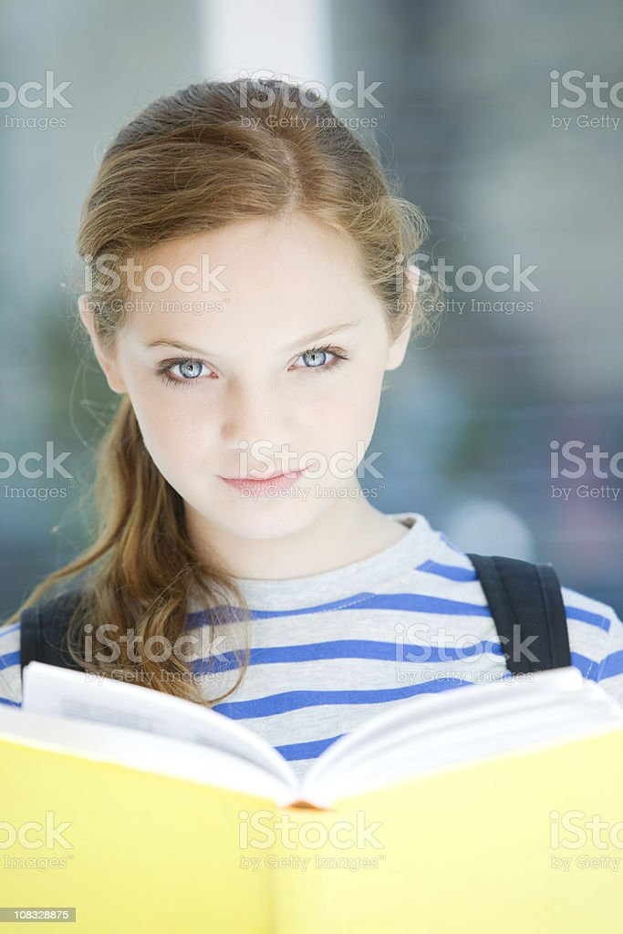 Teen Girl Smiling Looking at Camera Holding Book royalty-free stock photo