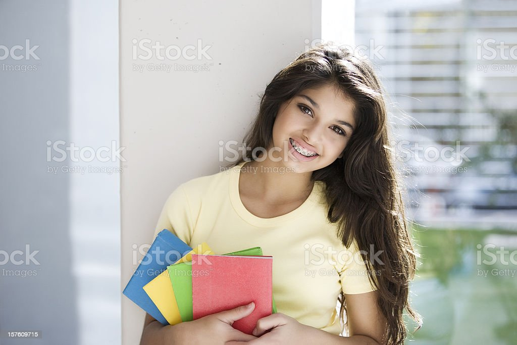 Teen Girl Smiling Looking at Camera Holding Books royalty-free stock photo