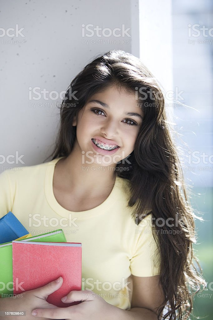 Teen Girl Smiling Looking at Camera Holding Books stock photo