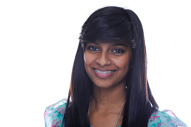 Teen girl smiling Smiling indian teen girl with brace on teeth suspenders stock pictures, royalty-free photos & images