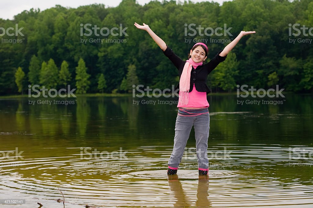 Teen girl standing in shallow water of a lake royalty-free stock photo