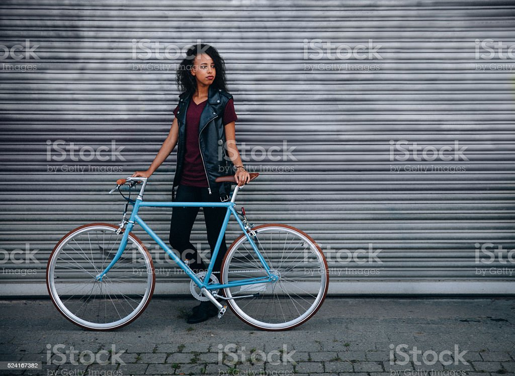 Teen girl standing with her bicycle on a city street stock photo