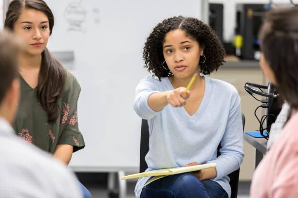teen girl takes question during serious high school study group - debate стоковые фото и изображения