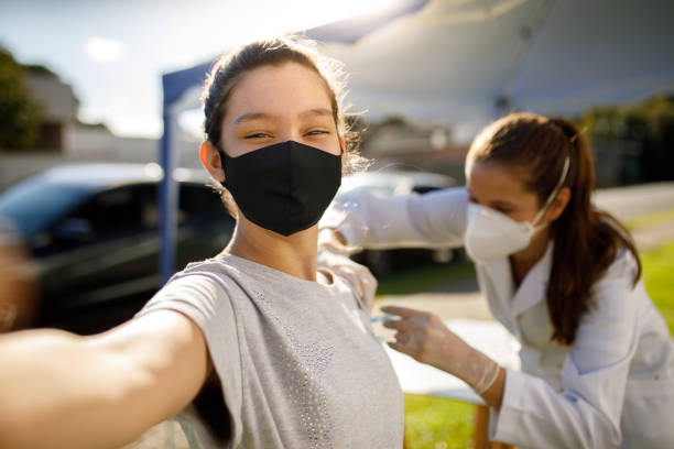 Teen girl taking a selfie while taking vaccine stock photo