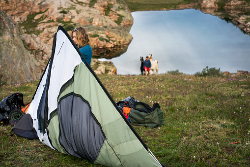 Blond teenage girl takes down her tent at camp while a female hiker ascends a steep grassy slope with two llamas from Eldorado Lake, at 12,500 ft elevation in the Grenadier Mountains, Continental Divide, San Juan Mountains, Rocky Mountains, Silverton, CO, USA