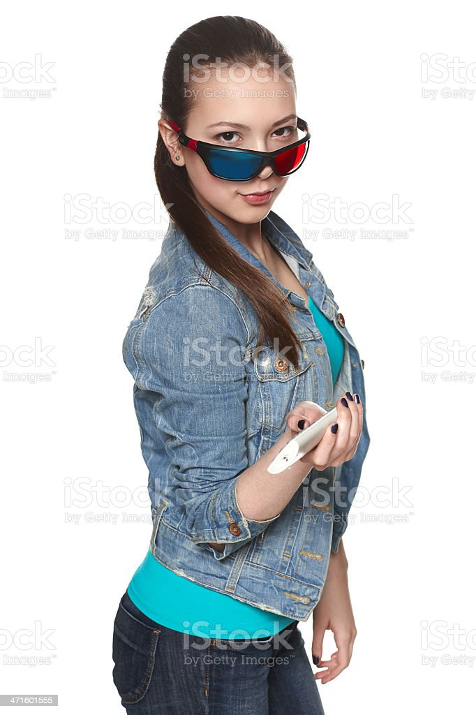 Teen girl wearing 3D glasses holding TV remote control royalty-free stock photo