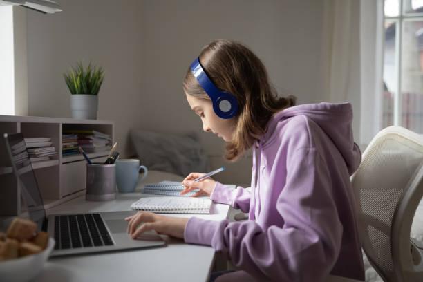 het meisje dat van de tiener hoofdtelefoons draagt die online van huis bestuderen dat nota's maakt - e learning stockfoto's en -beelden