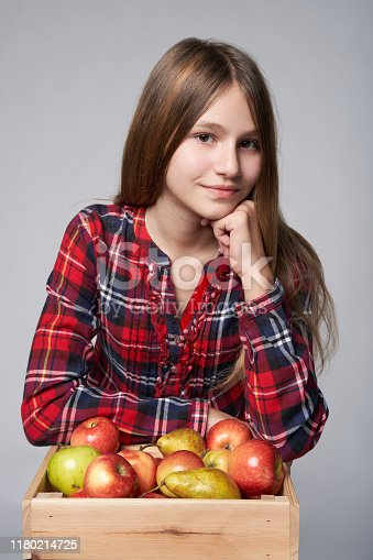 Children, healthy eating and food concept. Portrait a teen girl with apples and pears in a box, studio shot over grey background