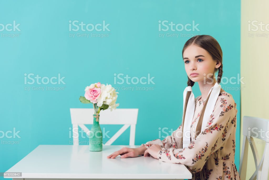 adolescente com tranças com vestido de verão, sentado à mesa com flores, em azul - foto de acervo