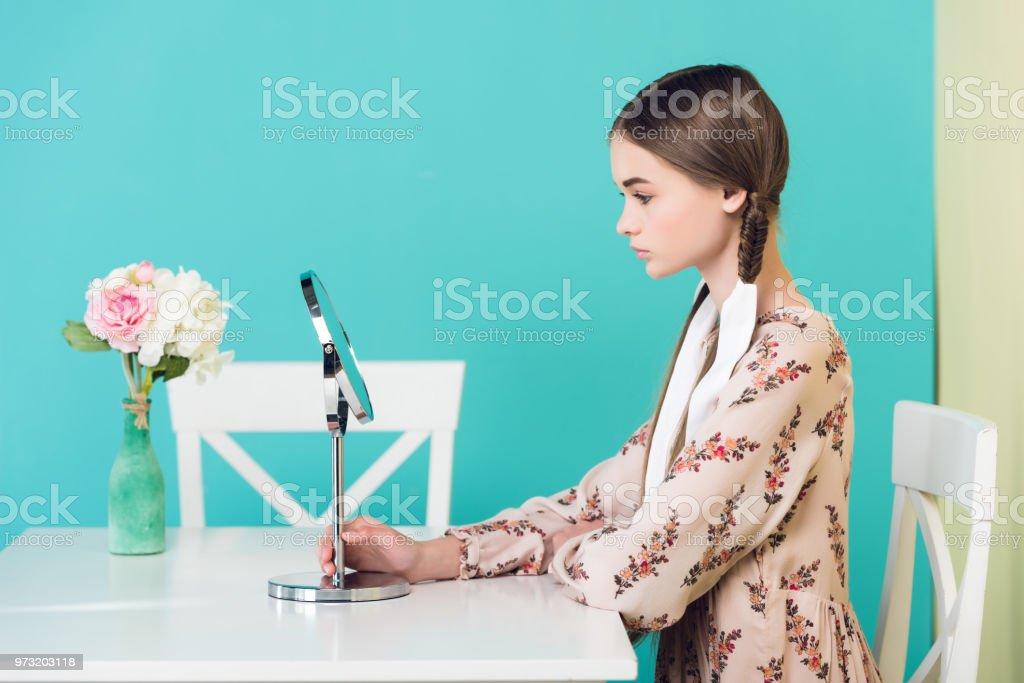 adolescente com tranças, olhando para o espelho enquanto está sentado na mesa com flores, isoladas em azul - foto de acervo