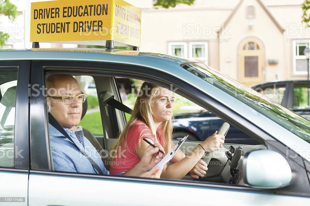 Teen Girl with Driver's Training Examiner in Student Driving Examination stock photo