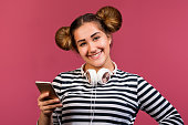 istock Teen girl with funny hairstyle use phone to listen the music on pink background 1125485678
