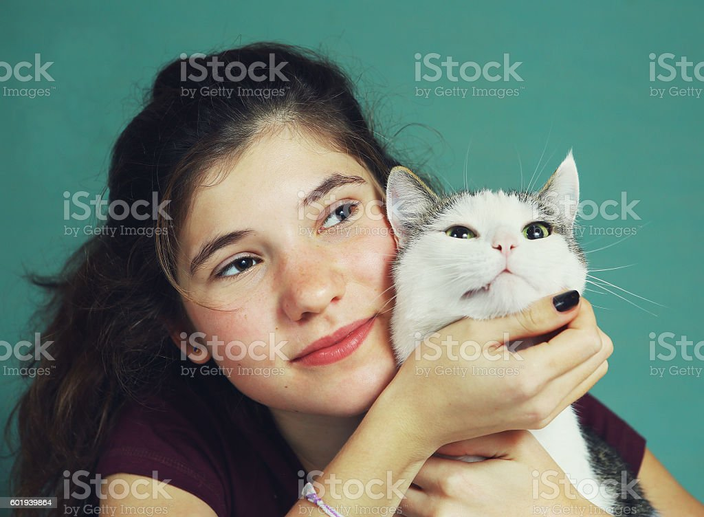 teen girl with long brown hair and cat stock photo