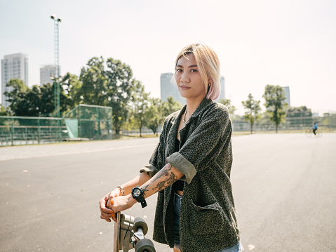 Japanese teenager with her skateboard at skateboard park in the morning getting ready to skate