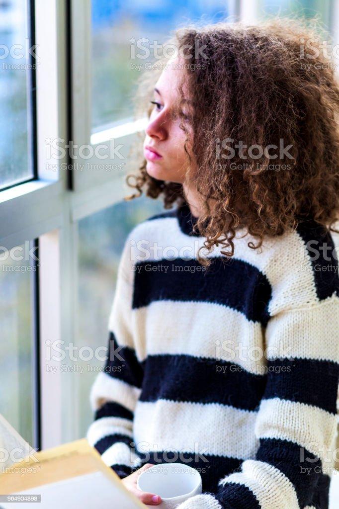 Teen girl with mug by window royalty-free stock photo