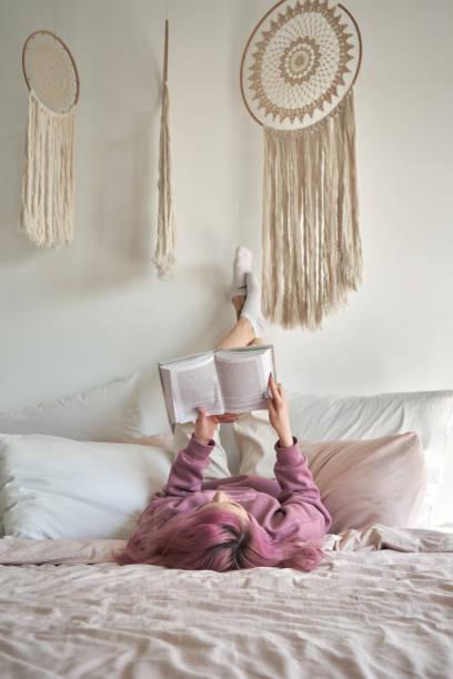 居心地の良い家で余暇に本を読んで足を持って快適なベッドに横たわっているピンクの髪を持つ十代の女の子。ヒップスターティーンエイジャーは、ドリームキャッチャーと居心地の良い寝� - gen z ストックフォトと画像