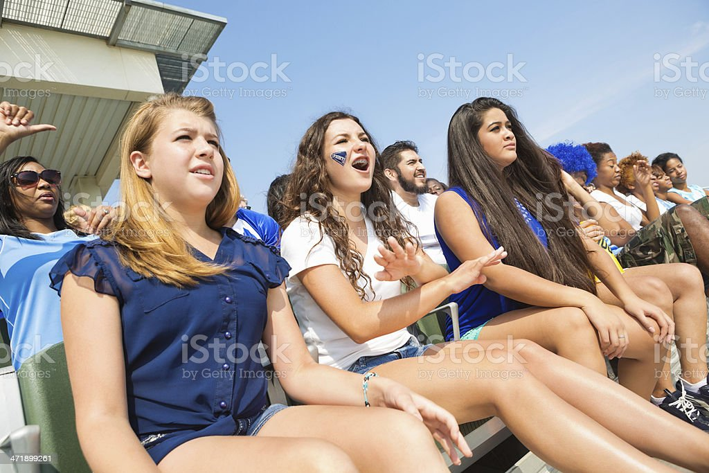 Teen girls cheering on sports team in high school stadium royalty-free stock photo