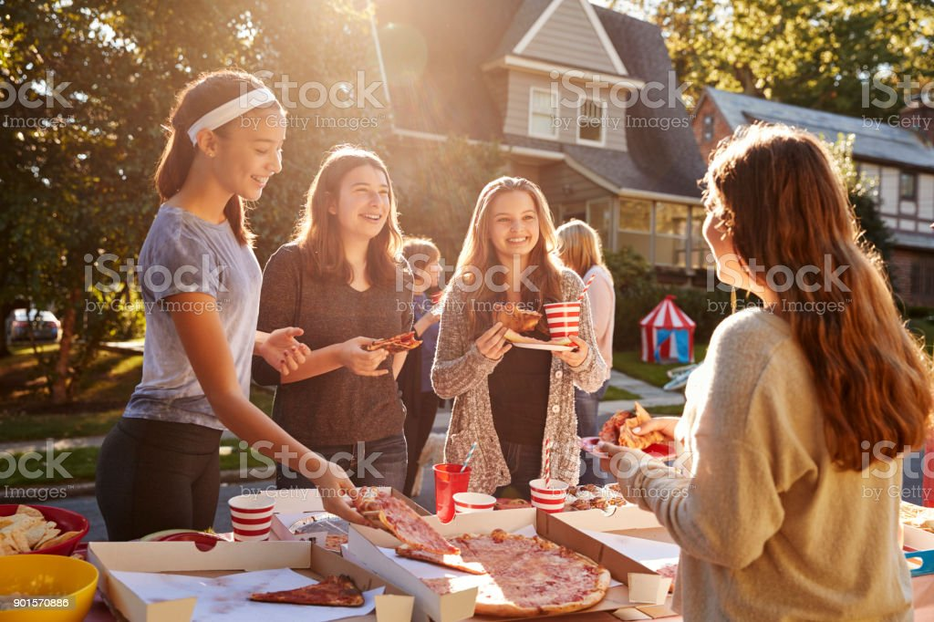 Teen girls eating pizza and talking at a block party stock photo