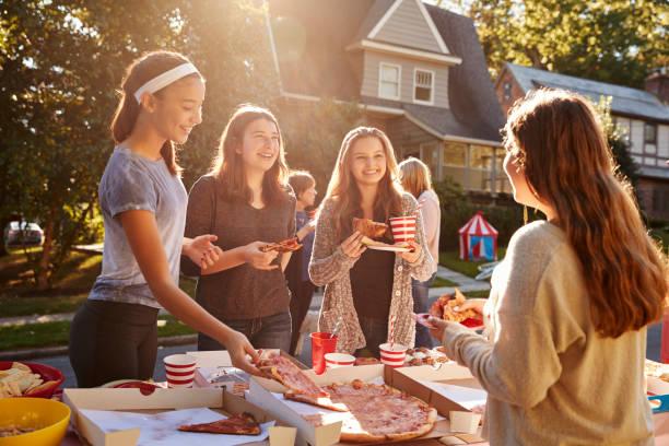 teen mädchen pizza essen und sprechen auf einer block-party - nachbar stock-fotos und bilder