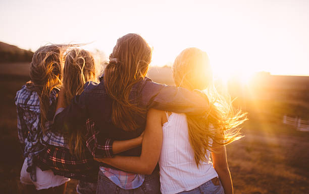 teen girls facing the sunset with on a summer evening - 少女 個照片及圖片檔