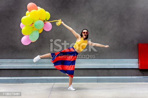 Young woman holding bunch of colorful balloons