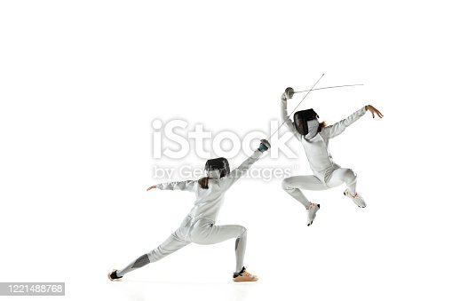 Teen girls in fencing costumes with swords in hands isolated on white studio background. Young female models practicing and training in motion, action. Copyspace. Sport, youth, healthy lifestyle.