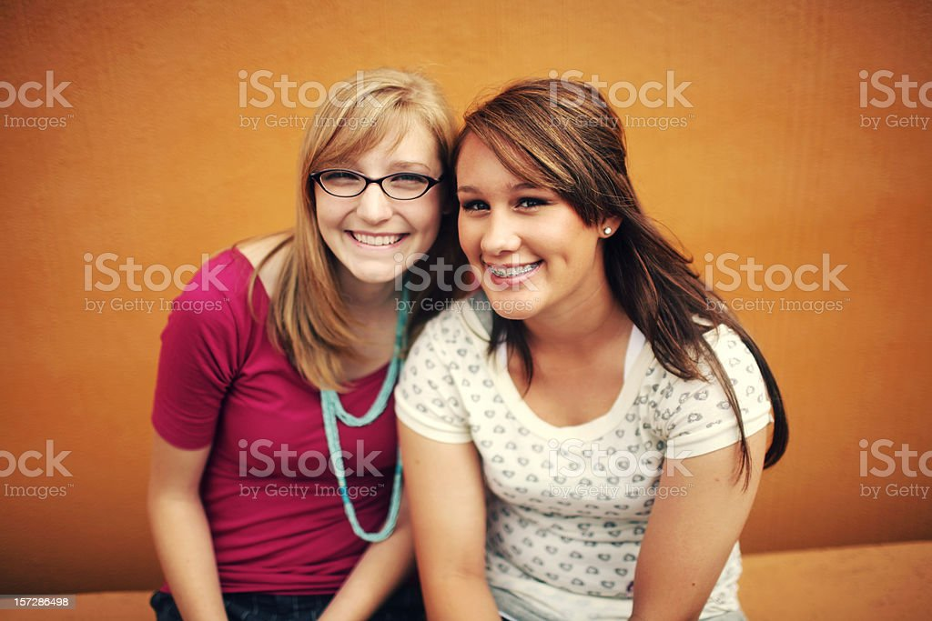 Teen Girls Laughing against Orange Wall royalty-free stock photo