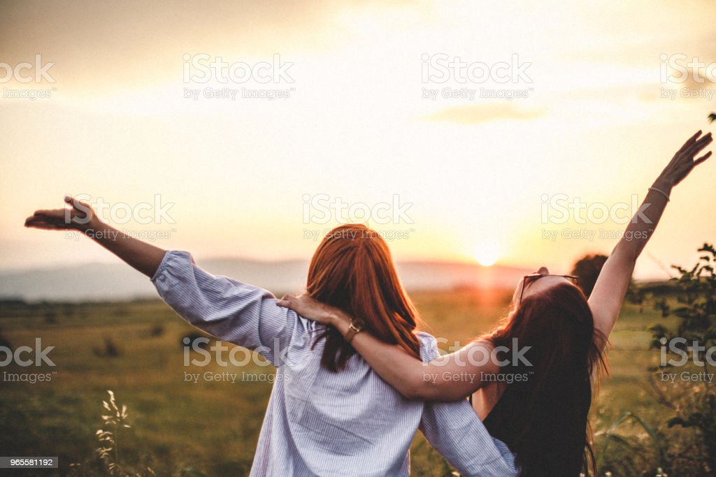 Teen girls look at the sunset stock photo