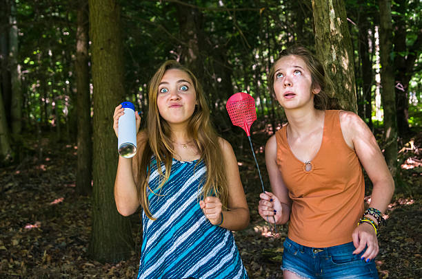 teen girls make faces chasing insects in a forest - mosquito stock photos and pictures