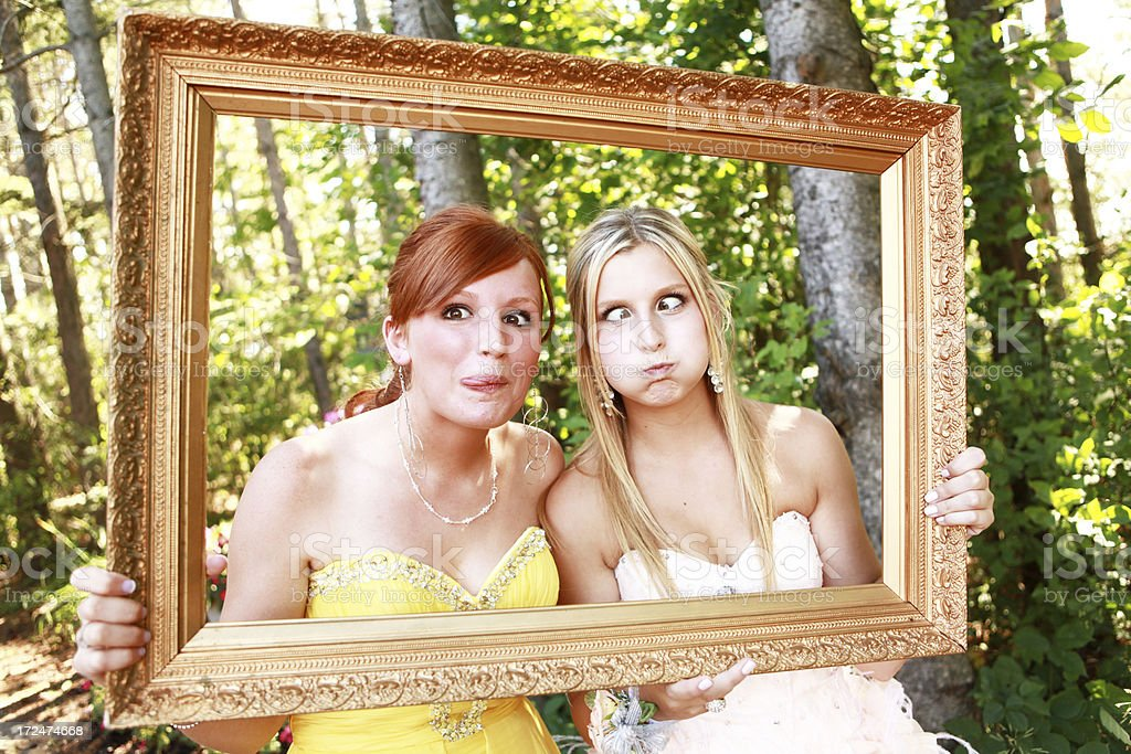 Teen Girls Making Funny Faces While Peeking Through Picture Frame royalty-free stock photo