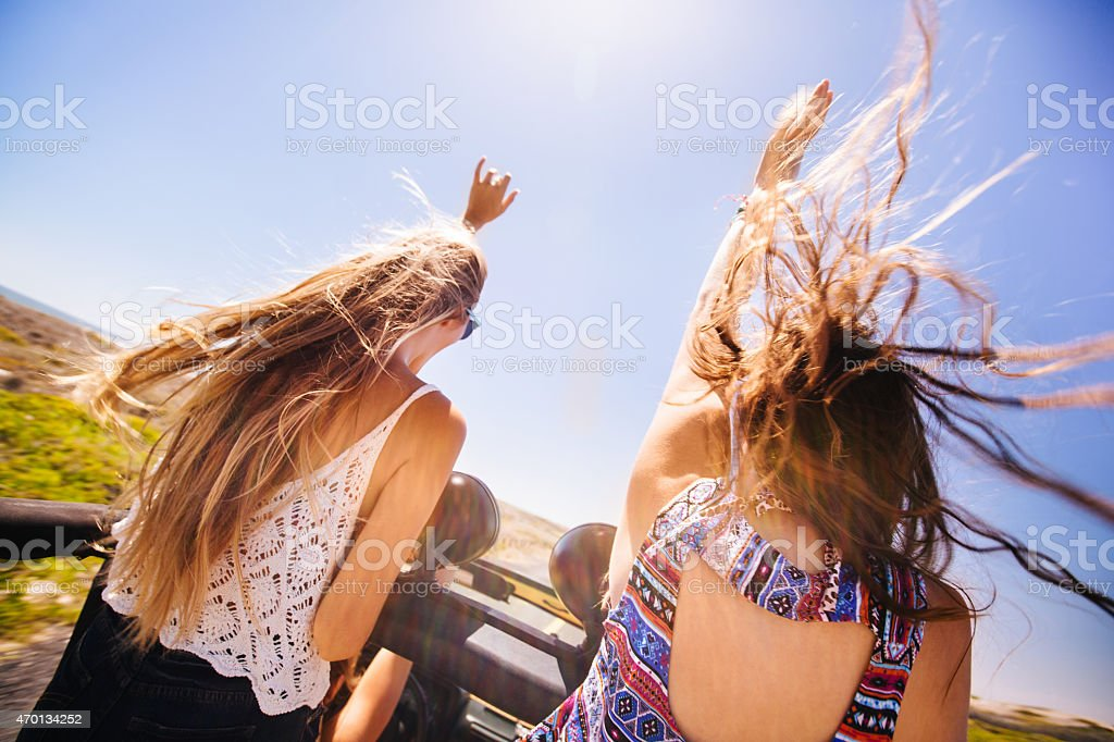 Teen girls on road trip with hair blowing in wind stock photo