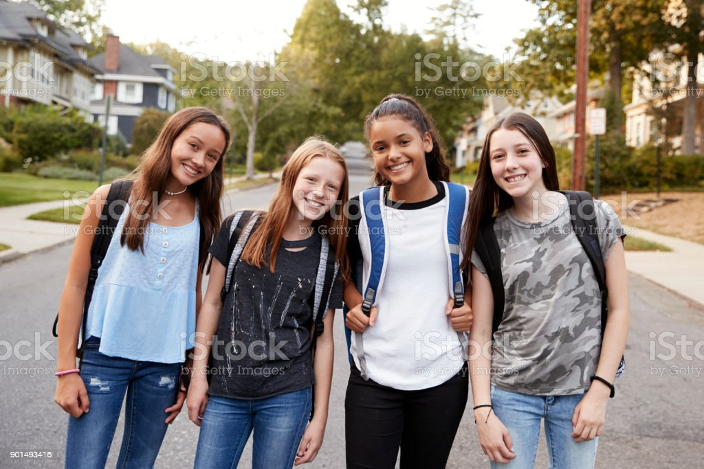 Teen girls on the way to school looking to camera, close up stock photo