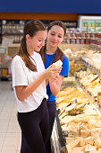 istock Teen girls shopping in supermarket reading product information. Choosing daily product 1090092312