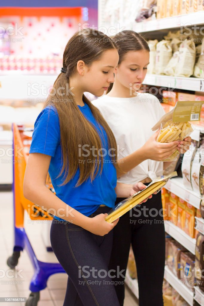 Teen girls shopping in the supermarket . Choosing daily product