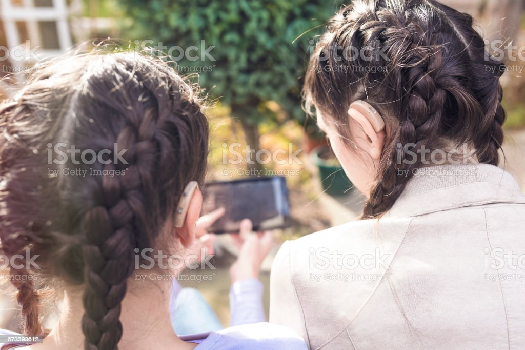 Teen girls with hearing aid - foto stock