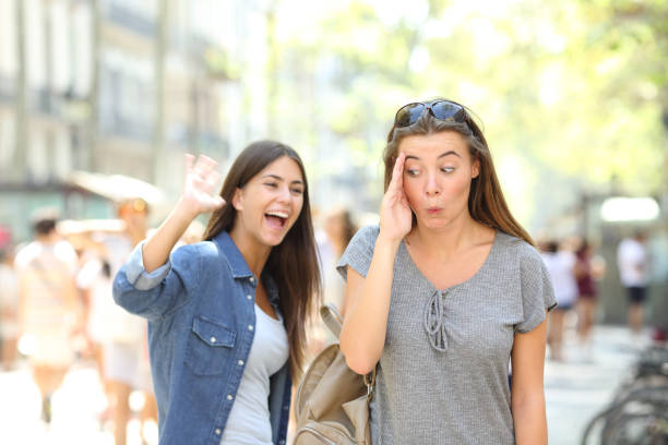 Teen greeting and friend ignoring her in the street Happy teen greeting waving hand and friend ignoring her in the street former stock pictures, royalty-free photos & images
