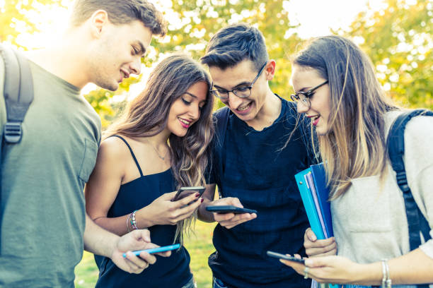 Teen group of friends with smartphones at park Teen group of friends with smartphones at park. Millennials using mobile phones, addicted to technology and social media. Lifestyle and friendship concepts digital native stock pictures, royalty-free photos & images