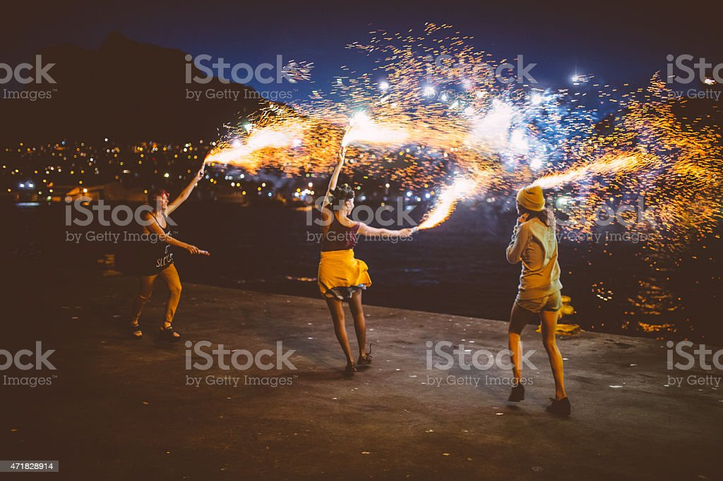 Teen grunge girls dancing with firework flares at night stock photo