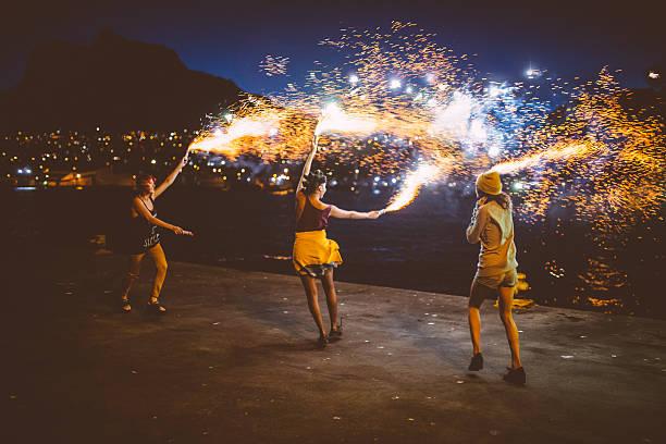 Teen grunge girls dancing with firework flares at night stock photo