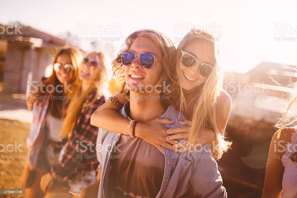 Teen guy piggybacking his girlfriend outdoors with friends stock photo