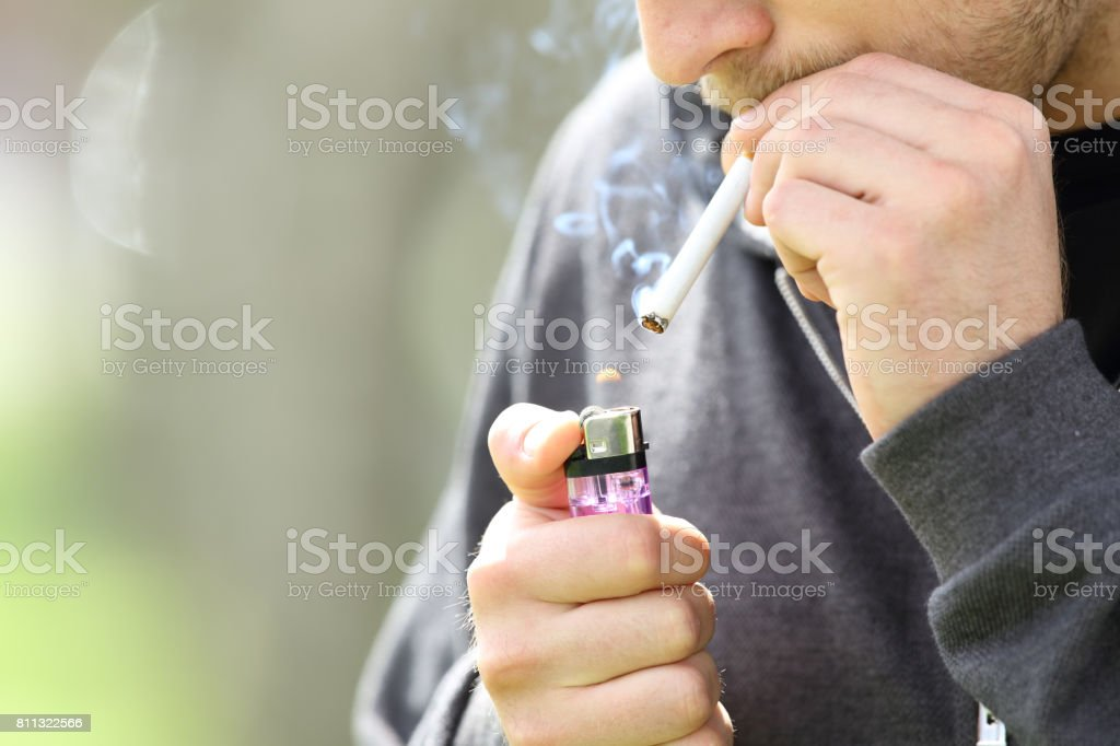 Teen hands lighting a cigarette to smoke stock photo