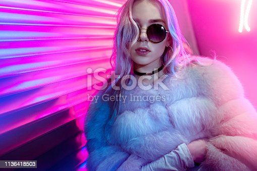 Teen hipster girl in stylish glasses and fur posing on street neon light wall background, female teenager fashion model woman with beautiful face looking at camera in city night light glow, back to 80s, portrait